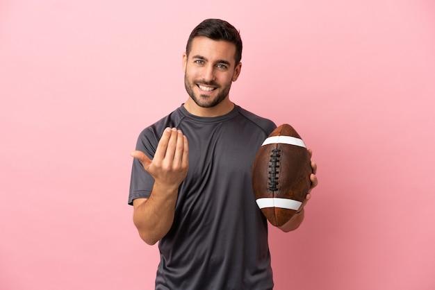 Giovane uomo caucasico che gioca a rugby isolato su sfondo rosa che invita a venire con la mano. felice che tu sia venuto