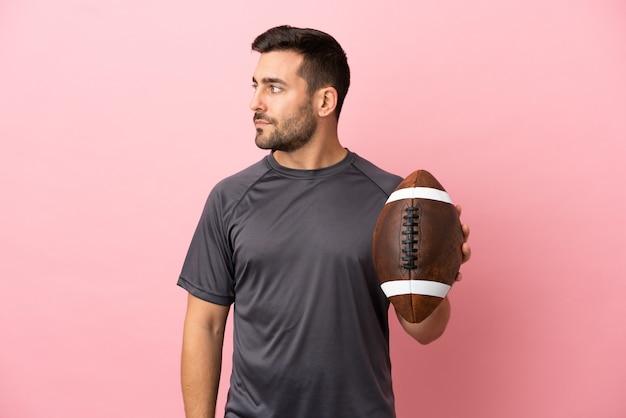 Giovane uomo caucasico che gioca a rugby isolato su sfondo rosa guardando di lato