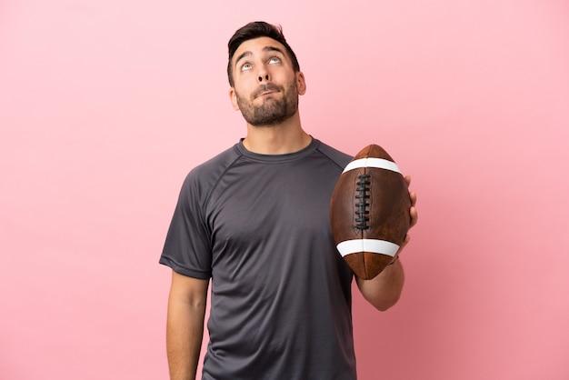 Giovane uomo caucasico che gioca a rugby isolato su sfondo rosa e alza lo sguardo