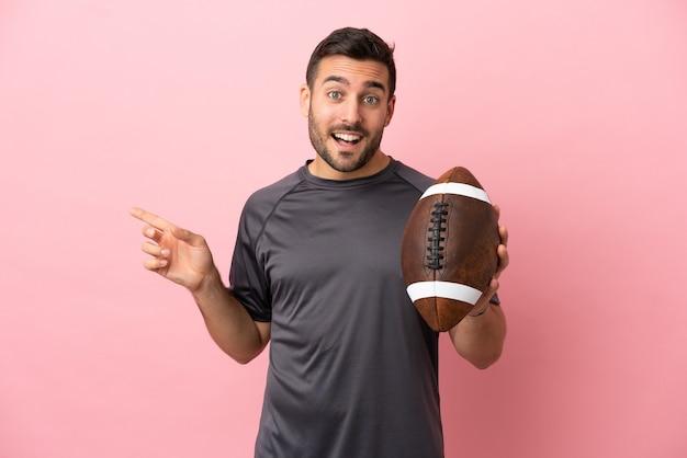 Giovane uomo caucasico che gioca a rugby isolato su sfondo rosa che punta il dito a lato