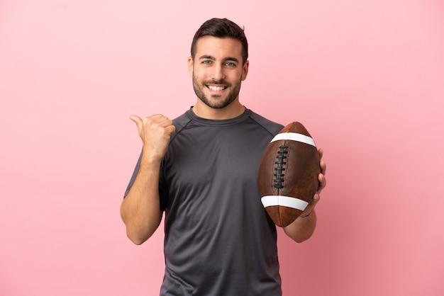 Giovane uomo caucasico che gioca a rugby isolato su sfondo rosa che punta al lato per presentare un prodotto