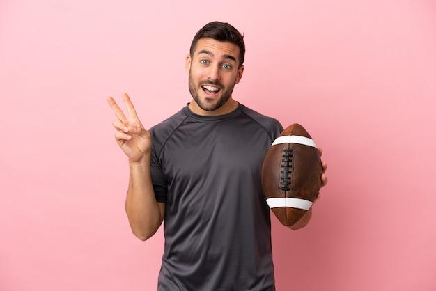 Giovane uomo caucasico che gioca a rugby isolato su sfondo rosa sorridendo e mostrando il segno della vittoria
