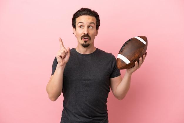 Giovane uomo caucasico che gioca a rugby isolato su sfondo rosa pensando a un'idea che punta il dito verso l'alto