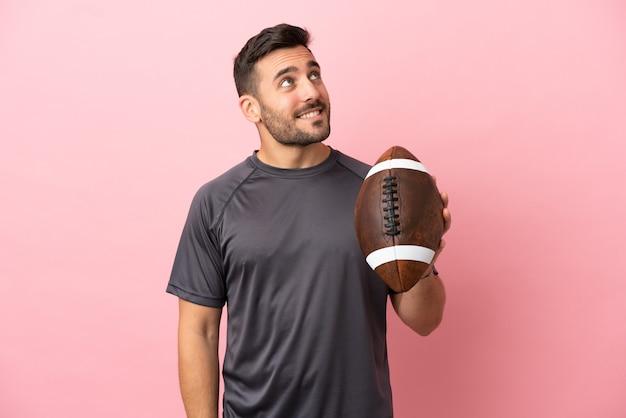 Giovane uomo caucasico che gioca a rugby isolato su sfondo rosa pensando a un'idea mentre guarda in alto