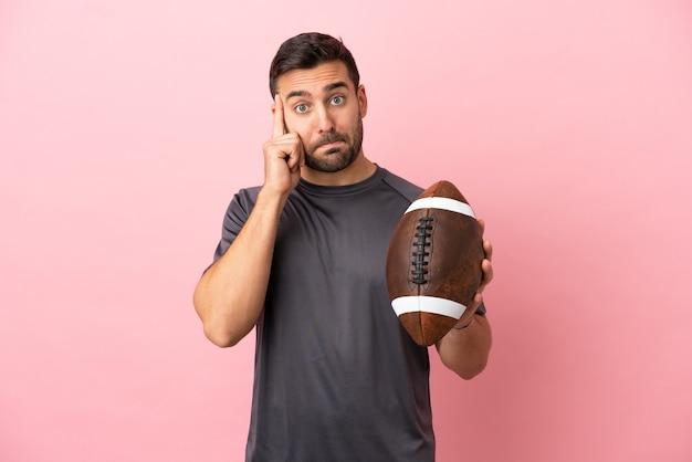 Giovane uomo caucasico che gioca a rugby isolato su sfondo rosa pensando a un'idea