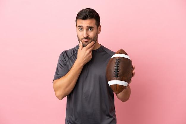 Giovane uomo caucasico che gioca a rugby isolato su sfondo rosa pensando