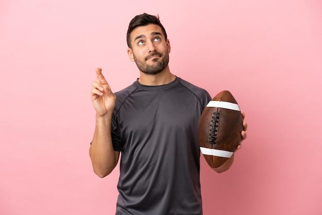 Giovane uomo caucasico che gioca a rugby isolato su sfondo rosa con le dita incrociate e augurando il meglio