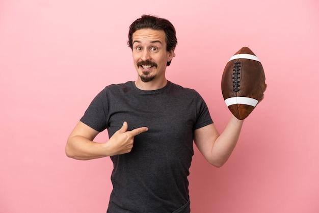 Giovane uomo caucasico che gioca a rugby isolato su sfondo rosa con espressione facciale a sorpresa