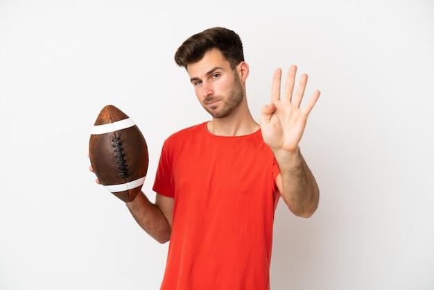 Giovane uomo caucasico che gioca a rugby isolato su sfondo bianco felice e conta quattro con le dita