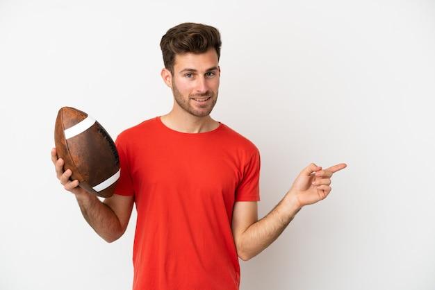 Giovane uomo caucasico che gioca a rugby isolato su sfondo bianco puntando il dito sul lato
