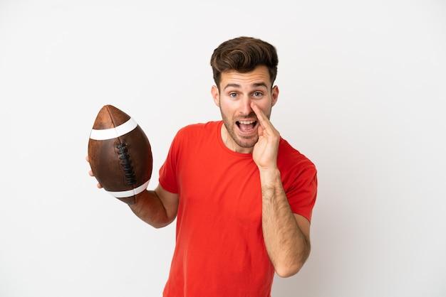 Giovane uomo caucasico che gioca a rugby isolato su sfondo bianco che grida con la bocca spalancata