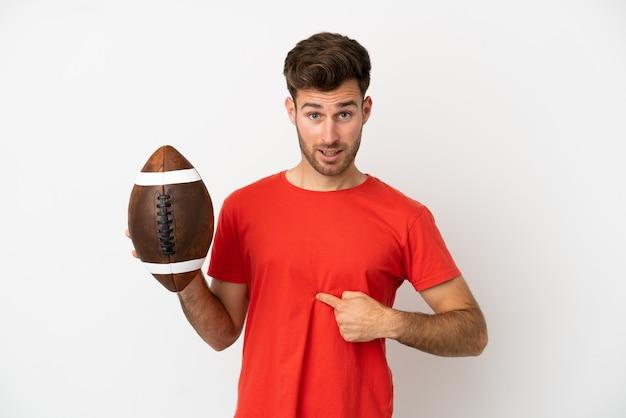 Giovane uomo caucasico che gioca a rugby isolato su sfondo bianco con espressione facciale a sorpresa