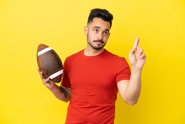 Giovane uomo caucasico che gioca a rugby isolato su sfondo giallo con le dita incrociate e augurando il meglio