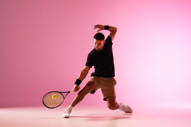 Giovane uomo caucasico che gioca a tennis isolato sul concetto di azione e movimento della parete rosa