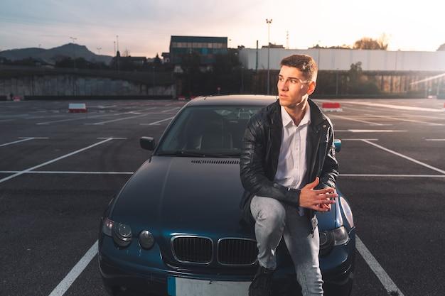 Giovane uomo caucasico in posa in un parcheggio con un'auto sportiva