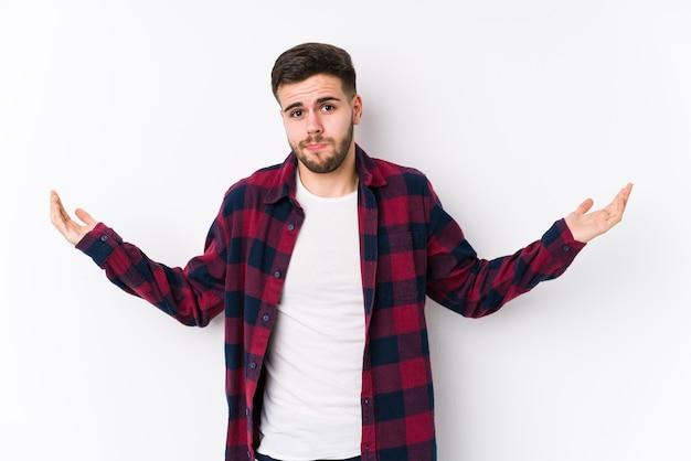 Il giovane uomo caucasico che posa in un muro bianco ha isolato dubitando e scrollando le spalle nel gesto interrogativo.