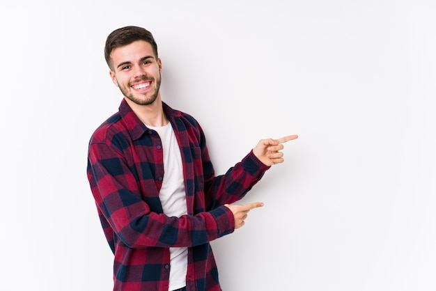 Il giovane uomo caucasico che posa in un muro bianco ha isolato l'eccitazione che indica con gli indici di distanza.