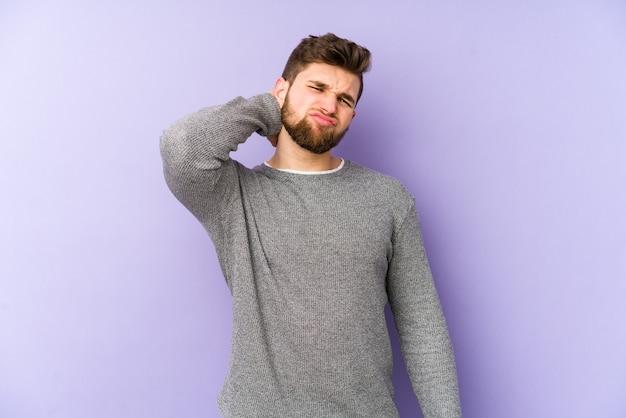 Giovane uomo caucasico su viola che ha un dolore al collo a causa dello stress, massaggiandolo e toccandolo con la mano.