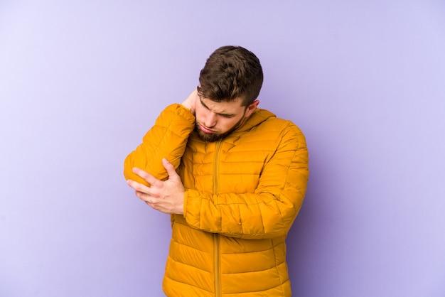 Giovane uomo caucasico sul gomito massaggiante viola, che soffre dopo un brutto movimento.