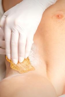 Giovane uomo caucasico che riceve la depilazione dall'ascella in un salone di bellezza depilazione uomini ascellare