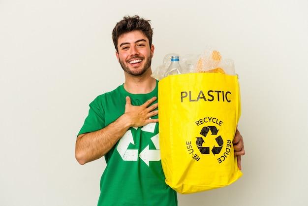 Il giovane uomo caucasico che ricicla plastica isolata su fondo bianco ride ad alta voce tenendo la mano sul petto.