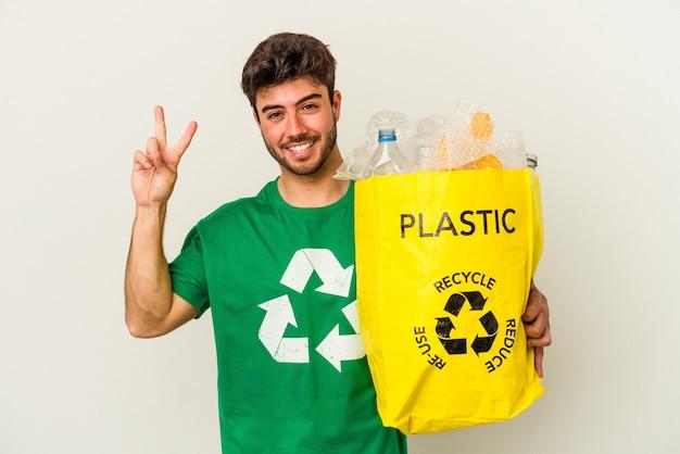 Giovane uomo caucasico che ricicla plastica isolata su sfondo bianco che mostra il numero due con le dita.