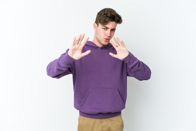 Giovane uomo caucasico che rifiuta qualcuno che mostra un gesto di disgusto.