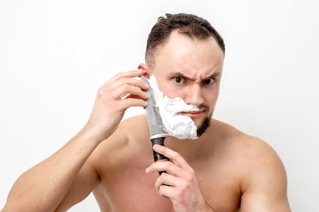Giovane uomo caucasico che rade la barba con il coltello su sfondo bianco