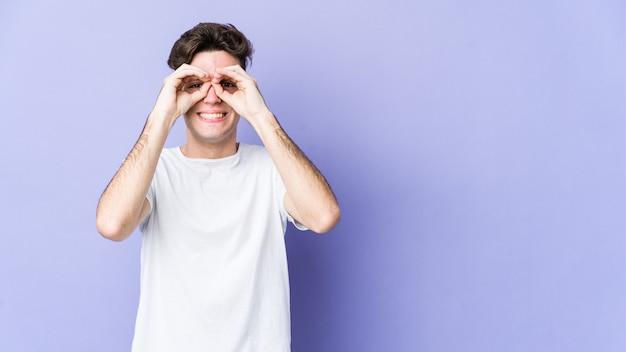 Giovane uomo caucasico che mostra il segno giusto sopra gli occhi