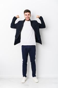 Giovane uomo caucasico che mostra gesto di forza con le braccia