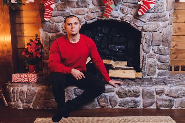Giovane uomo caucasico che si siede all'albero di natale decorato vicino alla tazza d'uso della tenuta del maglione del camino.