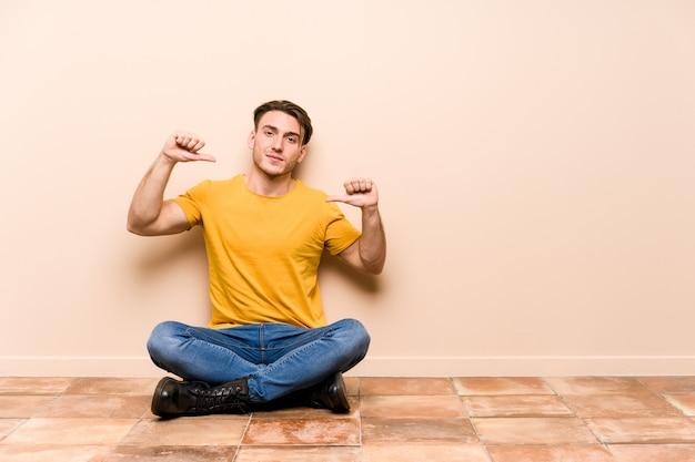 Il giovane uomo caucasico seduto sul pavimento isolato si sente orgoglioso e sicuro di sé, esempio da seguire.