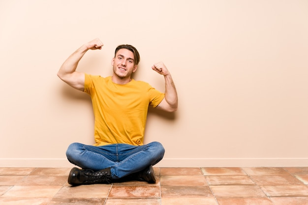 Giovane uomo caucasico seduto sul pavimento isolato mostrando il gesto di forza con le braccia, simbolo del potere femminile