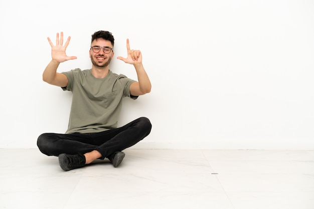 Giovane uomo caucasico seduto sul pavimento isolato su sfondo bianco contando sette con le dita