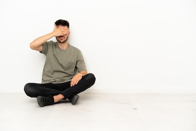 Giovane uomo caucasico seduto sul pavimento isolato su sfondo bianco che copre gli occhi con le mani. non voglio vedere qualcosa