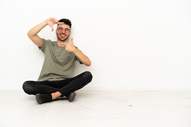 Giovane uomo caucasico che si siede sul pavimento isolato sul fronte bianco di messa a fuoco del fondo. simbolo di inquadratura
