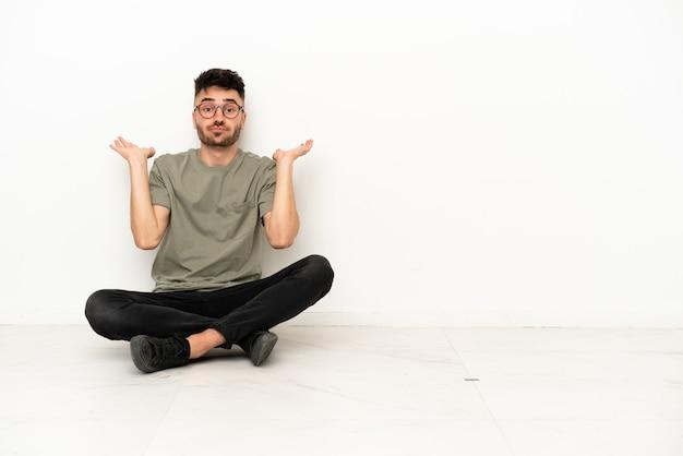 Giovane uomo caucasico seduto sul pavimento isolato su sfondo bianco avendo dubbi mentre alza le mani