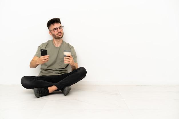 Giovane uomo caucasico seduto sul pavimento isolato su sfondo bianco che tiene il caffè da portare via e un cellulare mentre pensa a qualcosa