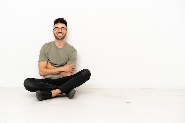 Giovane uomo caucasico seduto sul pavimento isolato su sfondo bianco tenendo le braccia incrociate in posizione frontale