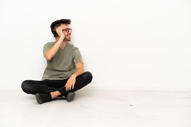 Giovane uomo caucasico seduto sul pavimento isolato su sfondo bianco mantenendo una conversazione con il telefono cellulare con qualcuno