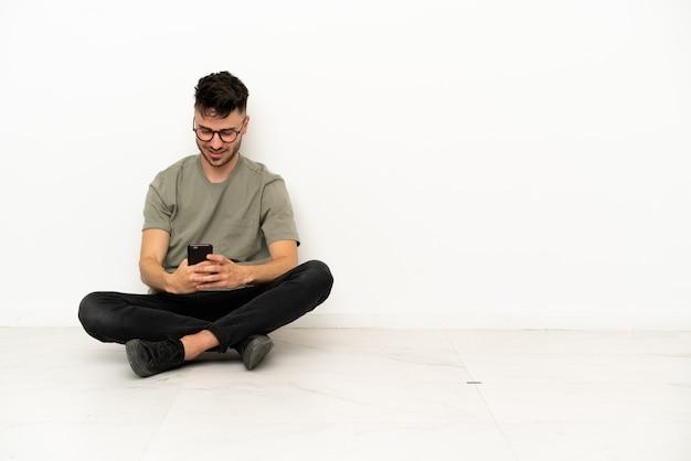Giovane uomo caucasico seduto sul pavimento isolato su sfondo bianco che invia un messaggio con il cellulare