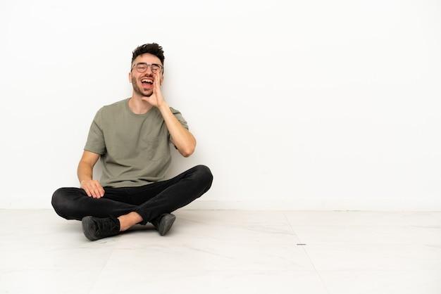 Giovane uomo caucasico seduto sul pavimento isolato su sfondo bianco che grida con la bocca spalancata