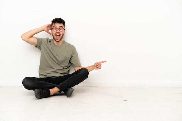 Giovane uomo caucasico seduto sul pavimento isolato su sfondo bianco sorpreso e puntando il dito di lato
