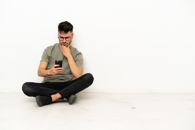 Giovane uomo caucasico seduto sul pavimento isolato su sfondo bianco pensando e inviando un messaggio