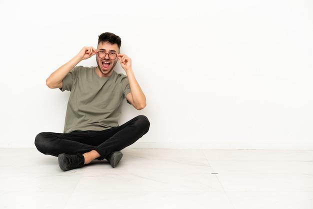 Giovane uomo caucasico seduto sul pavimento isolato su sfondo bianco con gli occhiali e sorpreso
