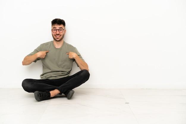 Giovane uomo caucasico seduto sul pavimento isolato su sfondo bianco con espressione facciale a sorpresa