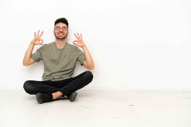 Giovane uomo caucasico seduto sul pavimento isolato su sfondo bianco in posa zen