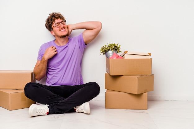 Giovane uomo caucasico seduto sul pavimento pronto per lo spostamento isolato su sfondo bianco toccando la parte posteriore della testa, pensando e facendo una scelta.