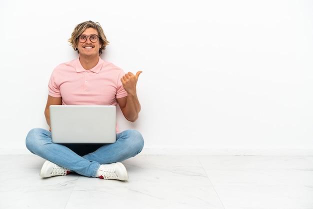 Giovane uomo caucasico seduto sul pavimento con il suo laptop isolato sul muro bianco che punta di lato per presentare un prodotto