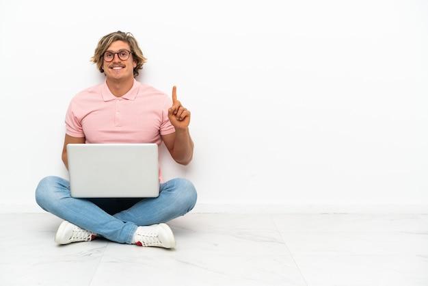 Giovane uomo caucasico seduto sul pavimento con il suo laptop isolato sul muro bianco rivolto verso l'alto una grande idea